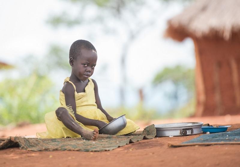 Jente på seks år i gul kjole som sitter på bakken og spiser fra en skål ved en stråhytte i en flyktningleir i Uganda.