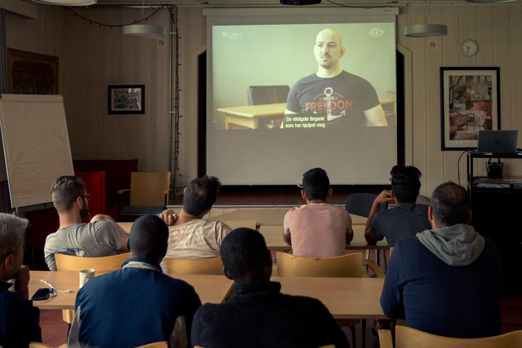 Beboere på Refstad asylmottak ser på filmintervju fra en enFASE