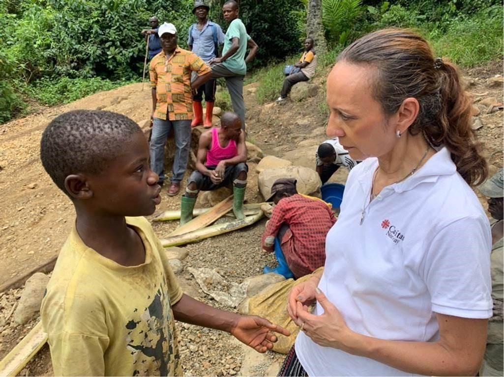 Generalsekretær i Caritas, Martha Rubiano Skretteberg snakker med et barn som jobber i gruvene i Øst-Kongo.