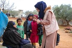 En lokal hjelpearbeider kommer med nødhjelp til en kvinne og hennes barn i Syria. Foto