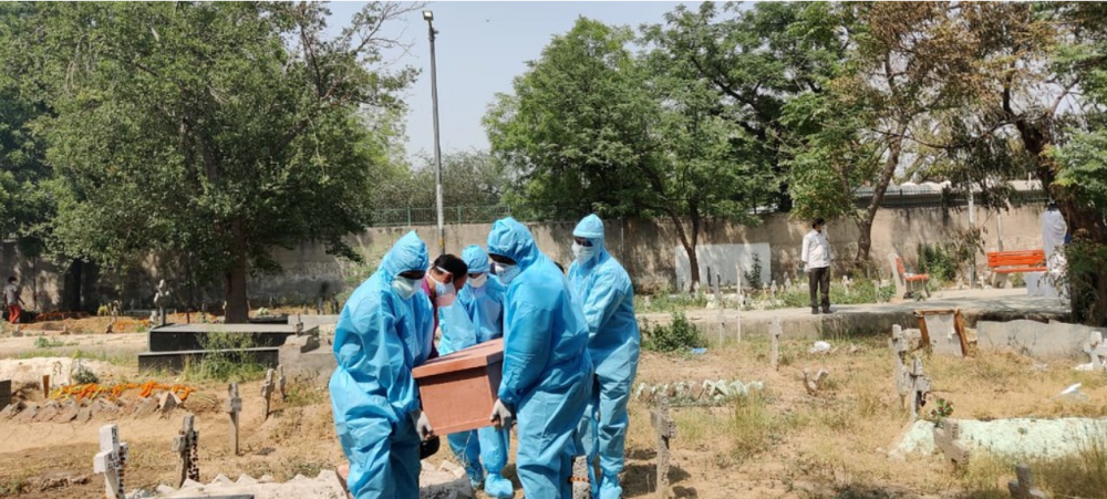Mennesker i verneutstyr bærer en kiste på en kirkegård i India.