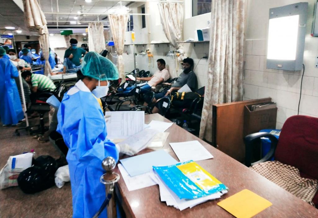 Sykehuspersonale i verneutstyr arbeider mellom pasienter i en gang i et sykehus i India.