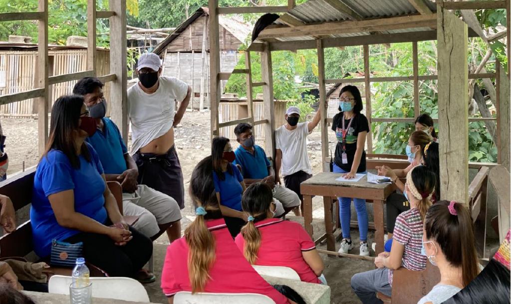 Bildet viser et møte mellom en ansvarlig person fra den lokale Caritasorganisasjonen og innbyggerne i en landsby rammet av vulkanutbruddet.