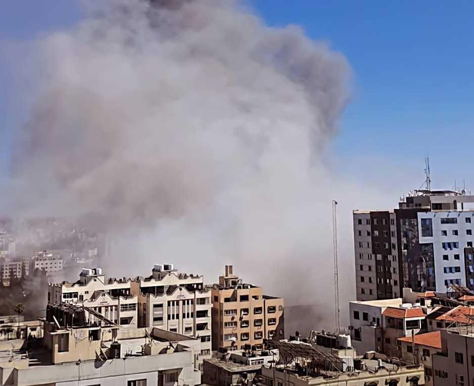 Støv og røyk i luften etter at en høyblokk har blitt bombet og raser sammen på Gaza.
