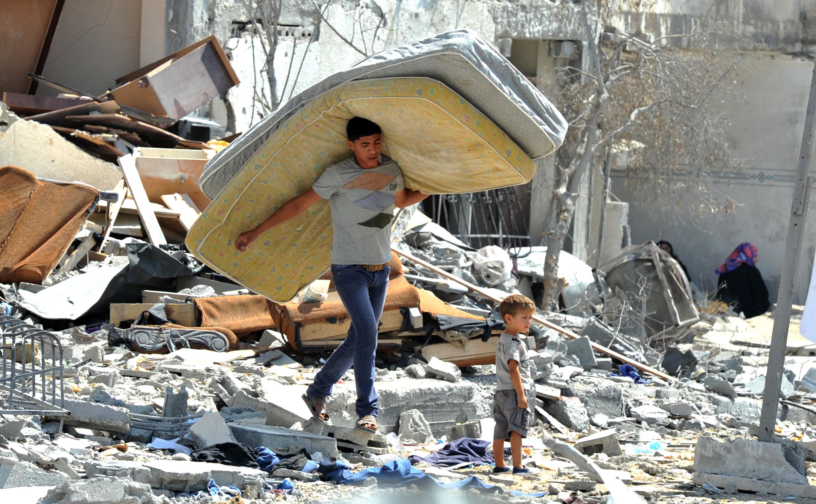 To palestinske barn går gjennom et utbombet hus på Gazastripen.