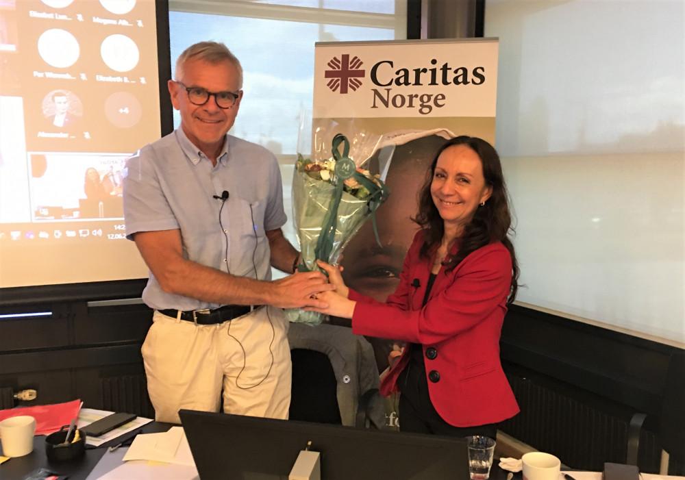 Styreleder Terje Osmundsen får blomster av generalsekretær Martha Rubiano Skretteberg etter åtte års innsats for Caritas Norge