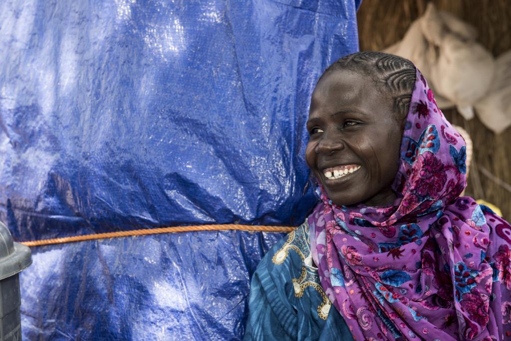 Bilde av en smilende nigersk kvinne ved hjemmet sitt.