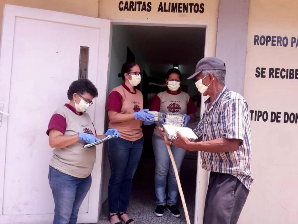 Tre arbeidere fra Caritas deler ut mat til en person i Venezuela.