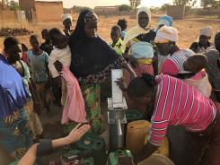 Kvinner og barn henter vann i en brønn i Mali.