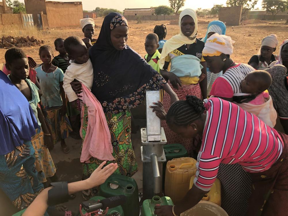 Kvinner og barn henter vann fra en brønn i Mali