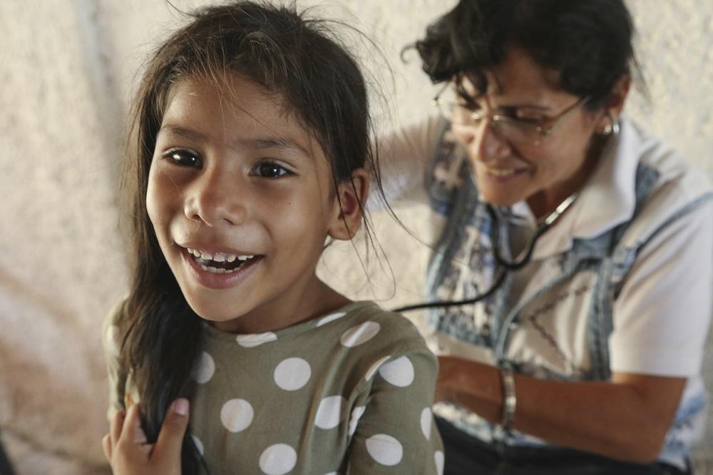 En ung jente får sjekket lungene med stetoskop av Dr Albina Rosas som er frivillig i Caritas Venezuela
