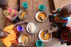 Bilde av fire barn fra Den sentralafrikanske republikk som sitter ved et bord og spiser fisk.