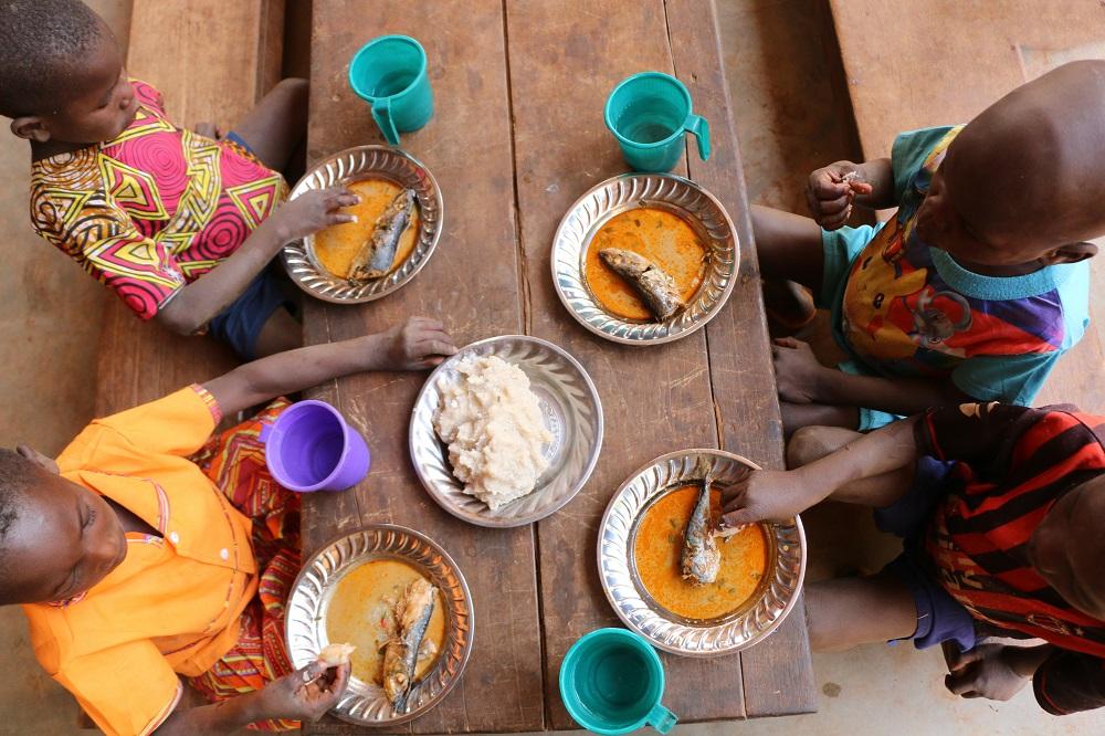 Bilde av barn fra Den sentralafrikasnke republikk som sitter ved et bord og spiser fisk.