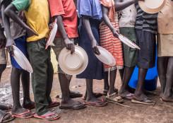 Bilde av barn som står i kø med tallerkenene sine for å få utdelt mat
