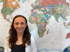 Martha Skretteberg ved siden av et verdenskart