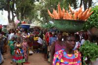 Bilde av kvinner på et marked med grønnsaksvarer.